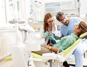 A dentist and dental assistant looking at a female patient's mouth