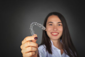 woman smiling holding an invisalign aligner