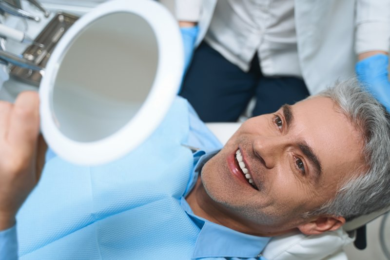 an older man lying back in the dentist's chair looking at his new smile in the mirror