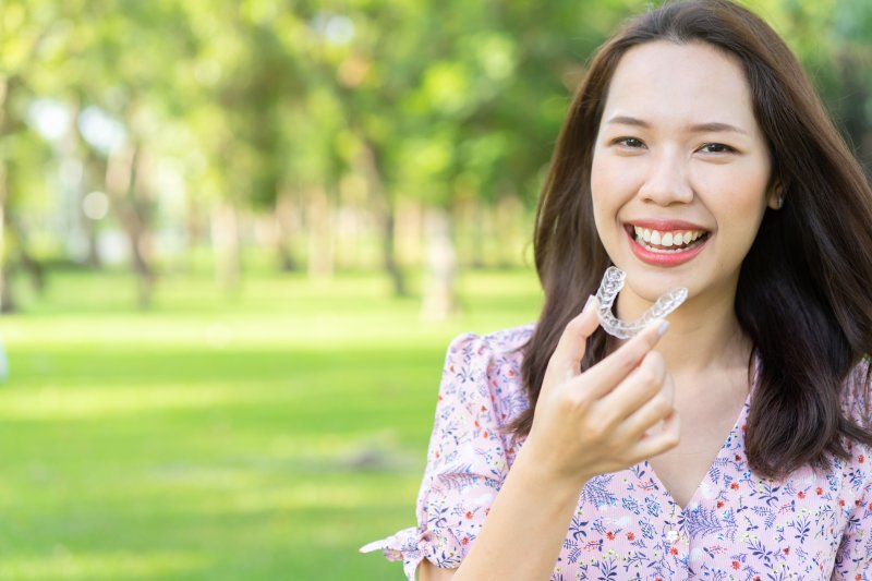 Woman in floral shirt smiling while holding Invisalign clear aligner