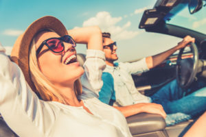Woman on road trip in car smiling
