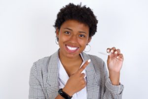 patient smiling and holding Invisalign